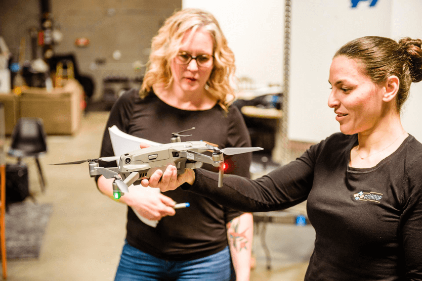 C2 Group's VP of Program Development, Nicole Alarcon, watches on as C2 President and Co-Founder Omneya Salem inspects a DJI Mavic 2. Image courtesy of C2 Group